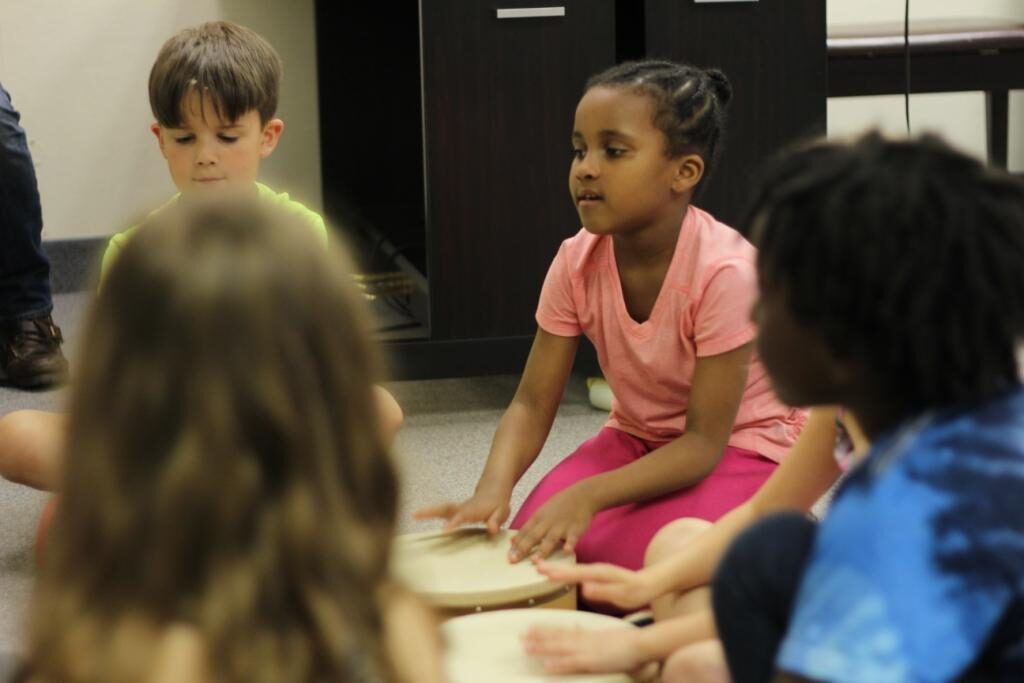 Children enjoying a drumming and singing activity during a Musikgarten group piano class.